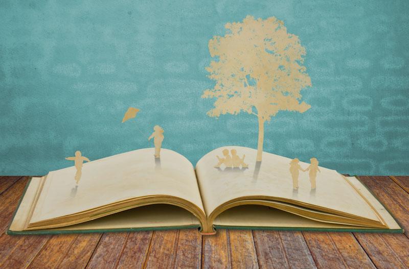 Libro con recortes de papel y niños en un parque